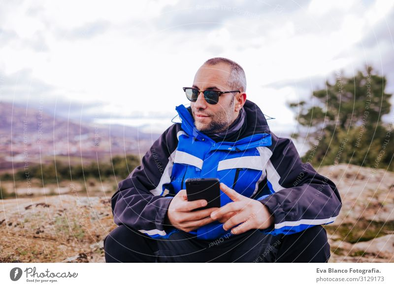 young hiker man using smart phone on top of the mountain. cloudy day Screen smart watch Hiking app ultra workout Fitness Lifestyle Practice device Sports