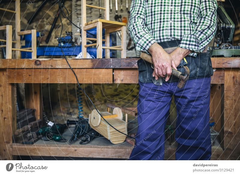 Unrecognizable carpenter holding a hammer Leisure and hobbies Chair Work and employment Profession Business Retirement Hammer Human being Man Adults Hand Old