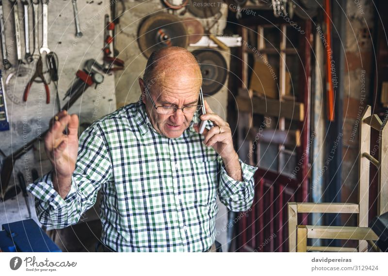 Carpenter in his workshop Chair Craft (trade) Business To talk Human being Man Adults Wood Old Authentic senior arguing cellphone mobile claiming Custom-made