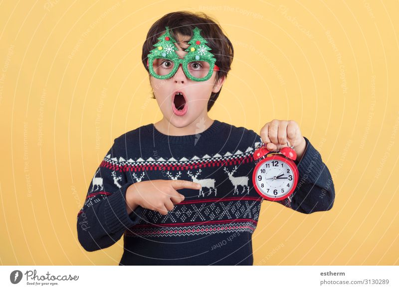 Surprised child with alarm clock Wearing Funny Christmas glasses Joy Winter Clock Feasts & Celebrations Christmas & Advent New Year's Eve Human being Masculine