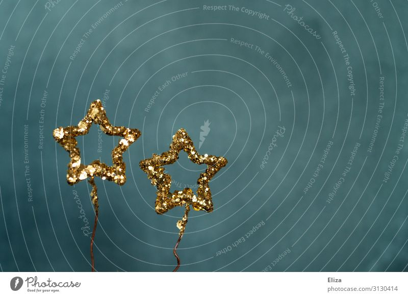 Two gold glittering stars against a blue background. Christmas, Advent, decoration. Decoration Christmas & Advent New Year's Eve Glittering Blue Gold Universe