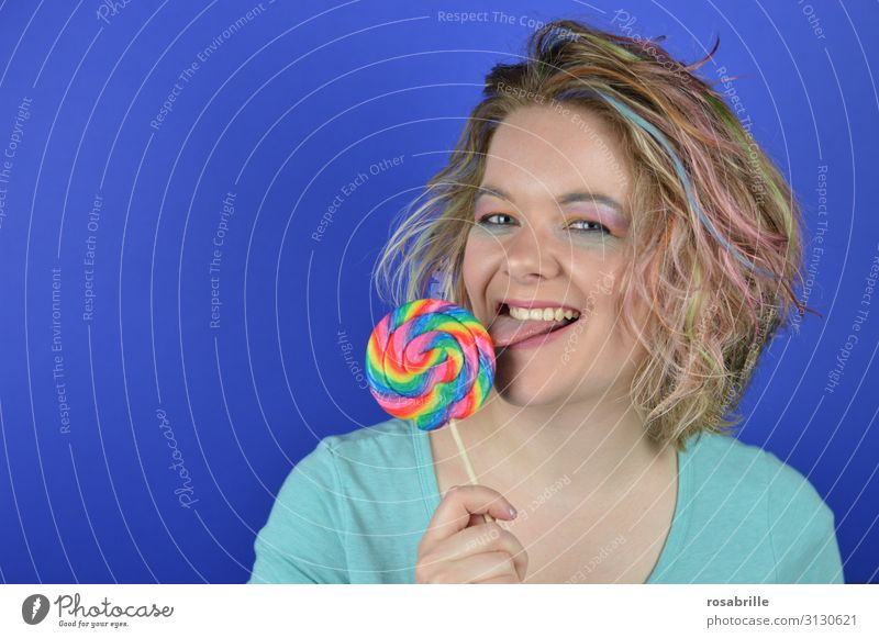 young blonde woman with coloured strands of hair biting into a giant lollipop Candy Joy Happy Beautiful Hair and hairstyles Make-up Contentment Carnival