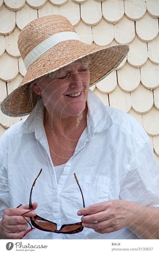 A mature woman with a straw hat on her head, holding a bright white blouse and sunglasses in her hand, is standing in the primordial course in front of an old house with white shingles. Lady is standing in front of a bright wall during a trip through the old town and smiles happily sideways down.