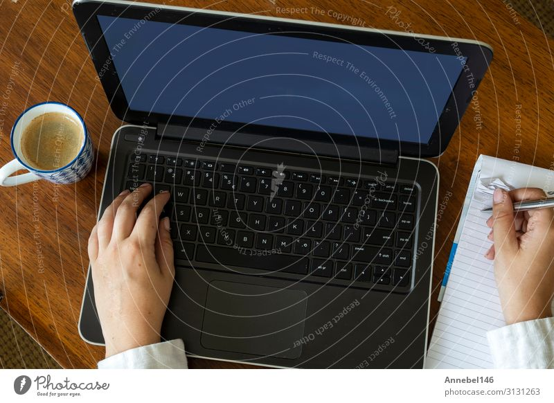 Top view of female using her laptop on a wooden table. Coffee Lifestyle Shopping Leisure and hobbies Desk Table Work and employment Workplace Office Business