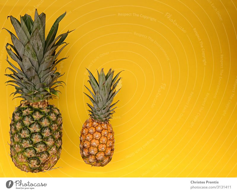 Pineapple with mini pineapple on a yellow ground. Food Fruit Dessert Eating Dinner Organic produce Diet Fitness Healthy Sweet Yellow Green Idea background
