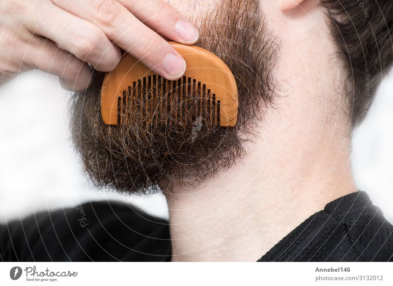 Closeup of a young man styling his long beard with a comb Lifestyle Style Hair and hairstyles Face Human being Masculine Man Adults Fashion Brunette Moustache