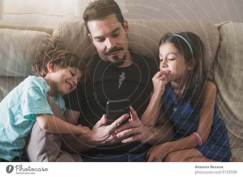 father phone Lifestyle Sofa Living room Child Telephone PDA Human being Boy (child) Man Adults Father Family & Relations Infancy Love Sit Together Modern