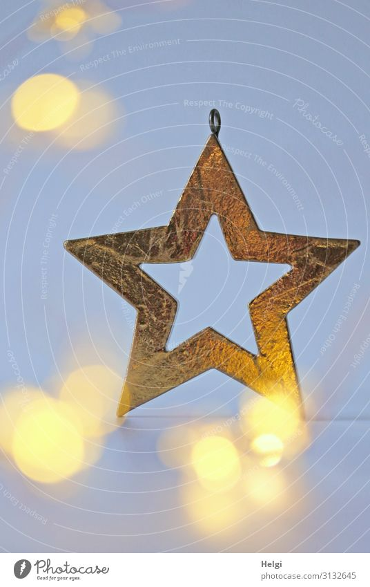 golden star as decoration in front of a light blue background with shining bokeh Christmas & Advent Decoration Sign Star (Symbol) Glittering Illuminate Esthetic