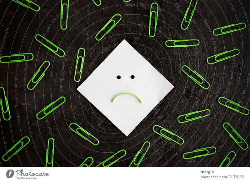 A smiley note surrounded by many green paper clips Work and employment Office work Workplace Green Black White Paper clip Smiley Pessimist Mouth Point Negative