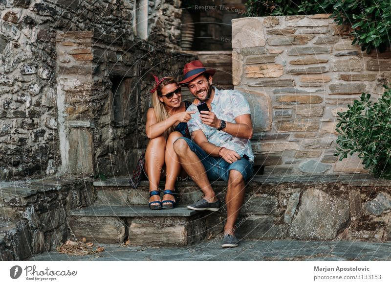 Young couple using smartphone on the steps of an old town Woman Human being Vacation & Travel Youth (Young adults) Man Young woman Young man Joy Lifestyle