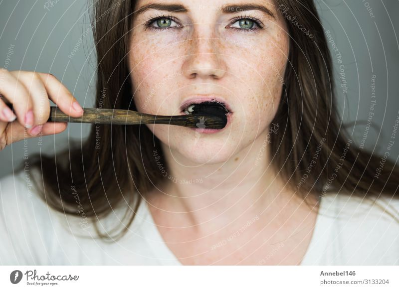 young woman brushing her teeth with a black tooth paste Happy Beautiful Health care Spa Bathroom Woman Adults Mouth Teeth Toothbrush Smiling Clean Black White