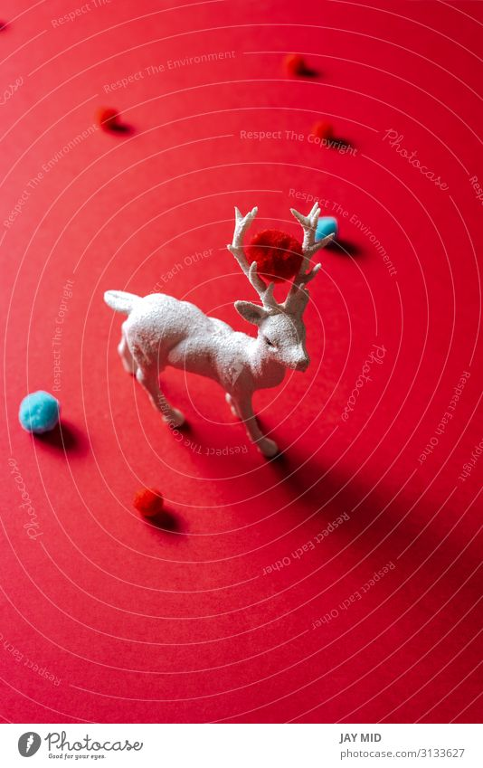 White reindeer toy with small balls of wool on red background Christmas & Advent Red Animal Winter Feasts & Celebrations Art Fashion Decoration Creativity Idea