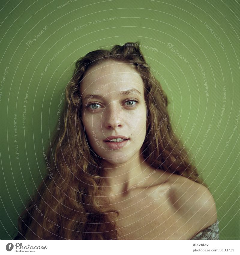 Rectangular portrait of a young woman in front of a green wall Style Beautiful Life Young woman Youth (Young adults) Face Model 18 - 30 years Adults Brunette