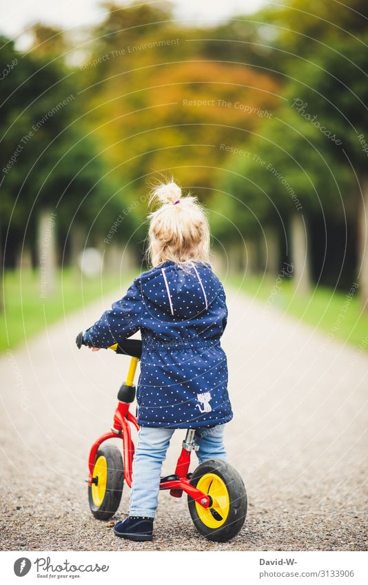 Child on the road with the bike Bicycle Kiddy bike Self-confident Bike helmet Safety Deep depth of field Lanes & trails off Driving Cycling Study