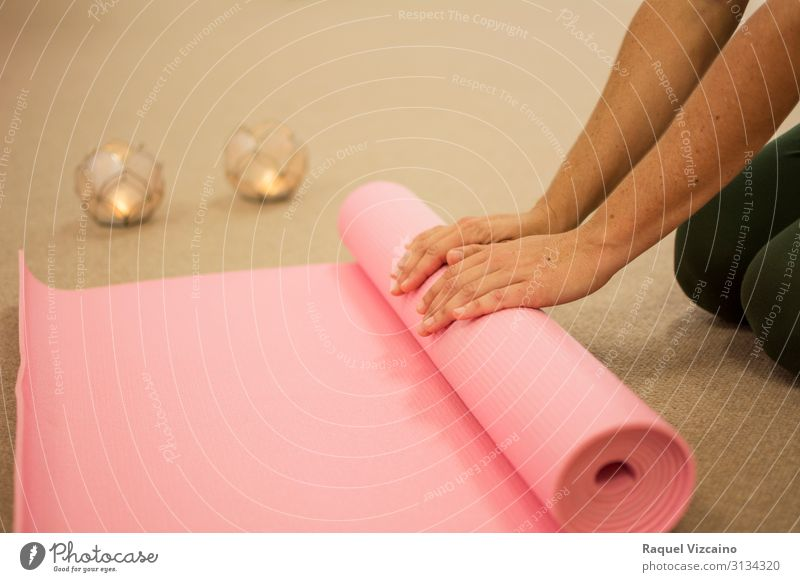 Woman's hands rolling up a pink yoga mat. Lifestyle Body Skin Health care Wellness Relaxation Meditation Spa Massage Sports Yoga Human being Adults Hand 1 Brown