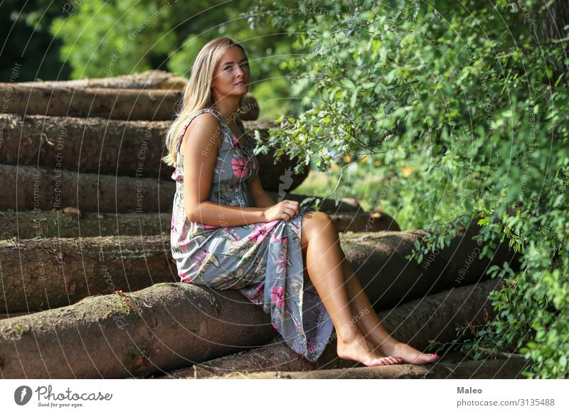 Girl sits on protocols Enchanting Attractive Beautiful Blonde Happiness Dress Cute Face Fashion Woman Forest Happy Lifestyle Model Nature Exterior shot Park