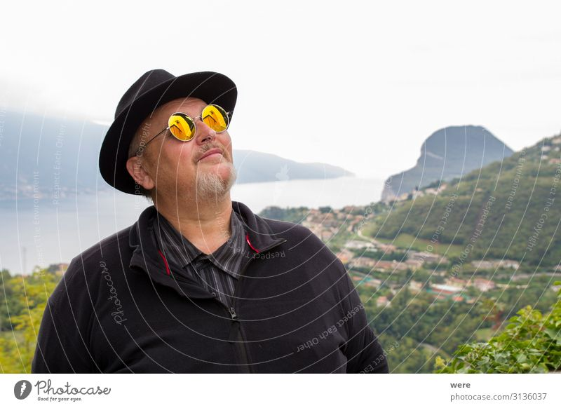 Old man in hat and sunglasses Human being To enjoy Dream bearded Granfather Lake Garda portrait Senior citizen bestager camera caucasian church church tower