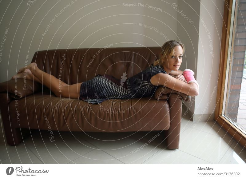 Beautiful young athletic slim woman lying on a brown sofa Style pretty Life Well-being Living or residing Sofa Room Young woman Youth (Young adults) Legs
