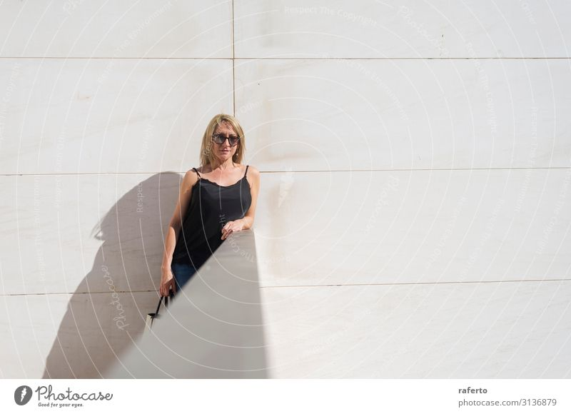 Blonde woman leaning on a white wall while looking camera Lifestyle Style Happy Beautiful Body Face Leisure and hobbies Summer Human being Feminine Young woman
