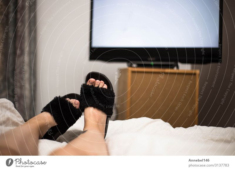 Person watches TV at night in bed with black Flip Flops. Beverage Joy Relaxation Leisure and hobbies Sofa Table Bedroom Entertainment Screen Technology