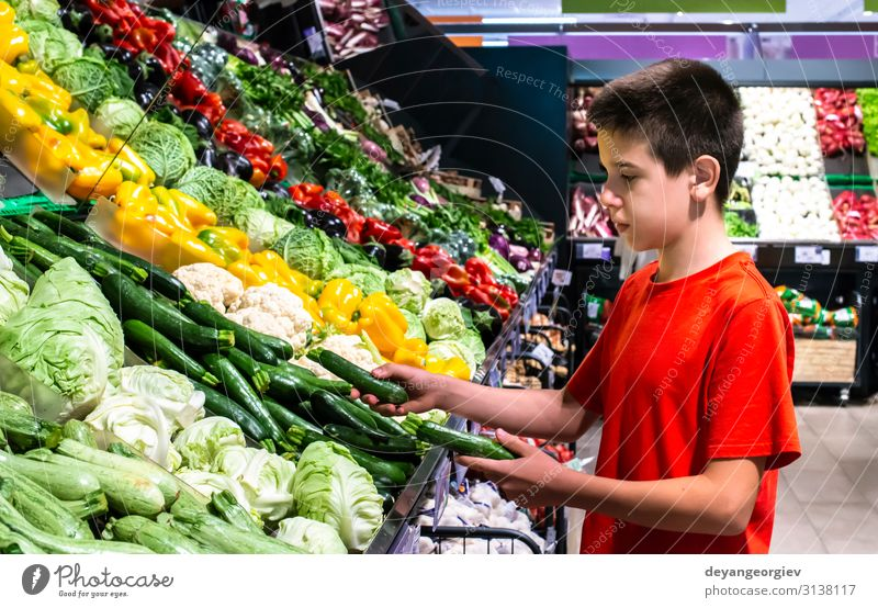 Child selecting vegetables on shelf in supermarket. Food Vegetable Vegetarian diet Shopping Marketplace Stand Fresh Natural shopper teenager kid healthy Variety