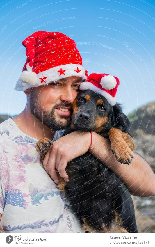 Man and his dog with Christmas hats. Human being Dog Christmas & Advent Blue White Red Animal Joy Winter Adults Love Friendship Cute Pet Hat