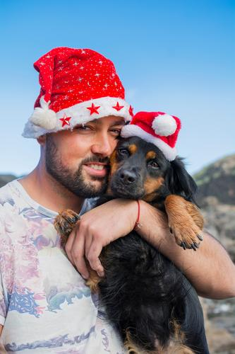Man and his dog with Christmas hats. Joy Winter Christmas & Advent Adults Friendship 1 Human being 30 - 45 years Animal Hat Pet Dog Love Cute Blue Red White