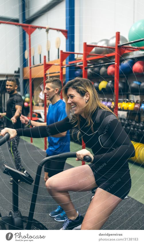 Sportswoman doing air bike at the gym Lifestyle Joy Happy Ball Human being Woman Adults Partner Fitness Smiling Authentic training cross fit Gymnasium mates