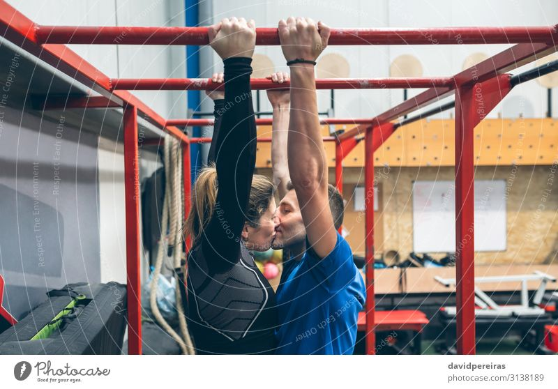 Couple kissing while exercising in the gym Lifestyle Body Sports Human being Woman Adults Man Fitness Kissing Love Athletic Authentic Strong Gymnasium Monkeys