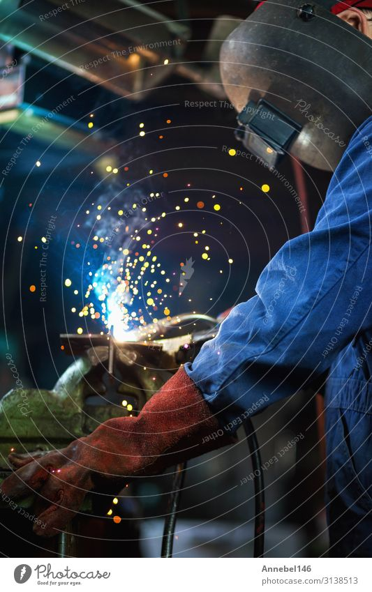 Welder is welding in the garage,industrial Worker Work and employment Profession Workplace Factory Industry Tool Technology Man Adults Metal Steel Build Make