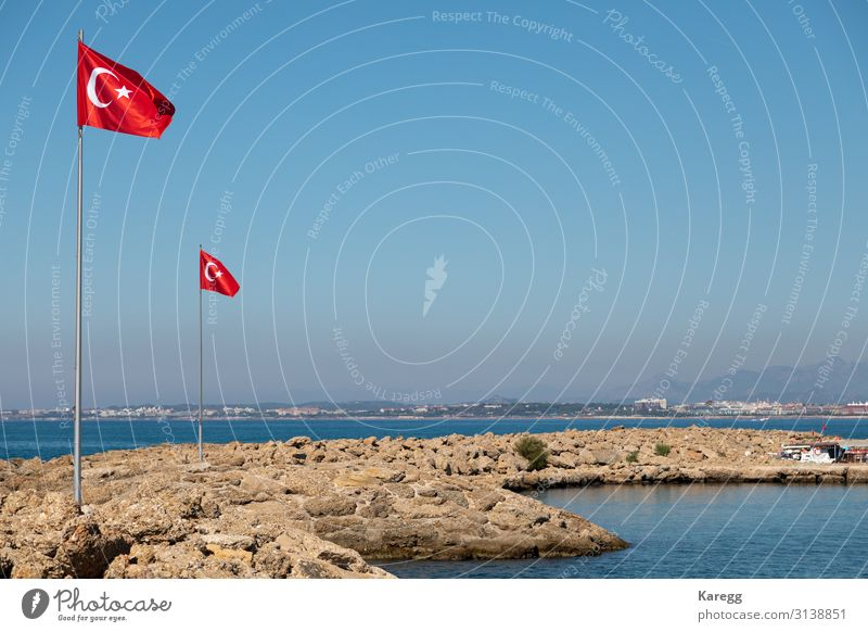 in the port of Side the Turkish flag blows at a mast Vacation & Travel Success Downtown Flag Blue Brown Red Modern memorial monument City architecture