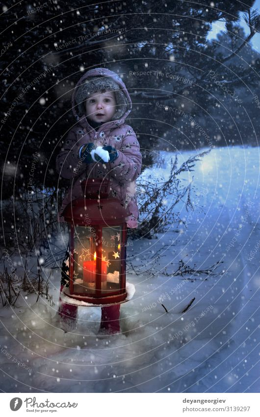 Child hold christmas lamp with glass and candle inside in the night to pine tree. Winter Snow Decoration Lamp Christmas & Advent Snowfall Tree Candle Old Dark