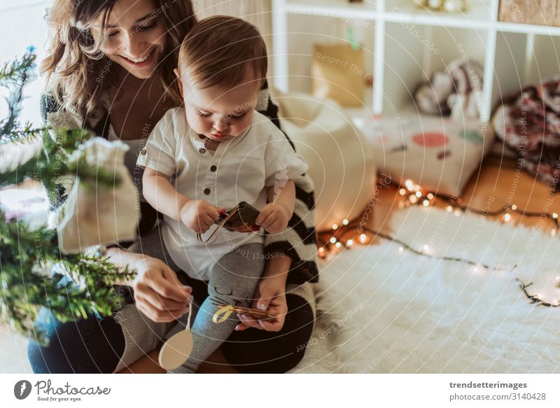 Mother and baby playing around the Christmas tree Family Baby Latin hispanic luck New Year Child Daughter Public Holiday Woman celebration mama Room Home