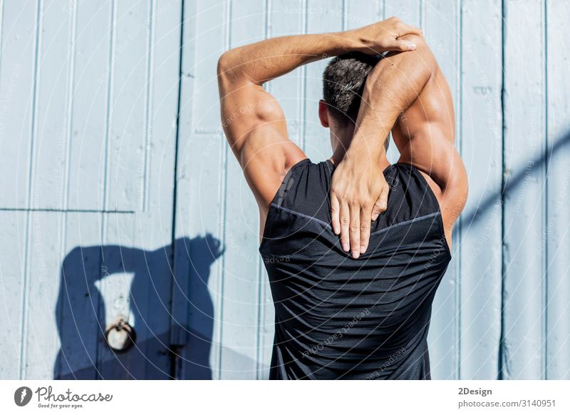 Young Man stretching against a blue wall after a workout outdoors Relaxation Sports Human being Masculine Young man Youth (Young adults) Adults Arm Hand 1