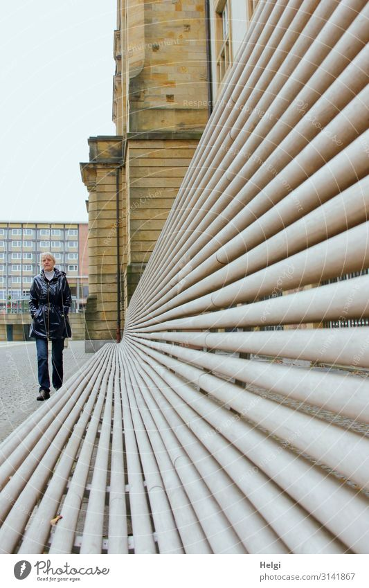 Perspective shot of a long bench in front of a building and a walking woman with a rain jacket and jeans Human being Feminine Woman Adults Female senior 1