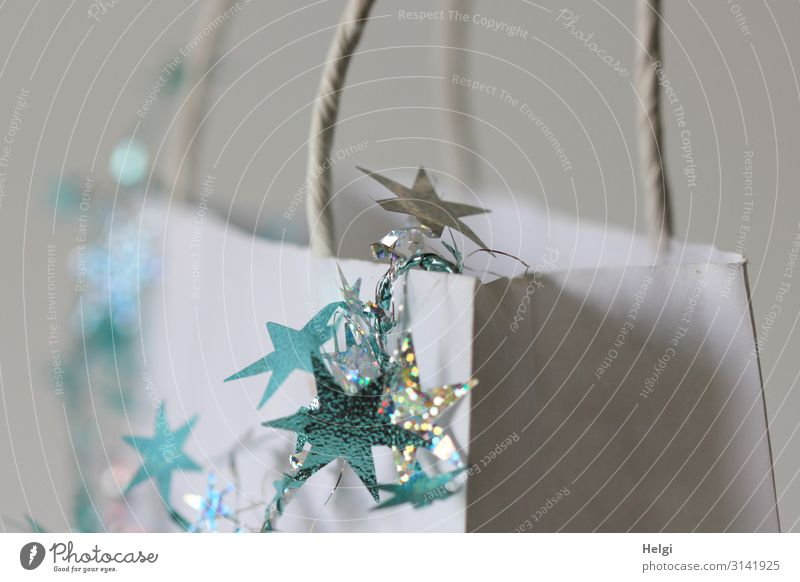 turquoise and silver stars hang as decoration on a white paper bag Feasts & Celebrations Christmas & Advent Paper Decoration Paper bag Star (Symbol) Gift Sign