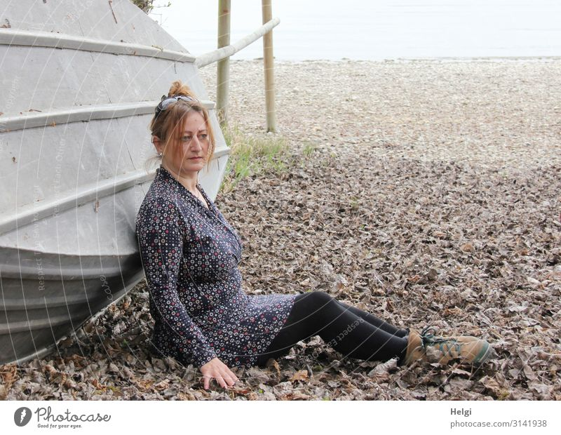 Woman with brunette hair pinned up in the leaves sitting in front of an overturned boat Human being Feminine Adults 1 45 - 60 years Environment Nature Landscape