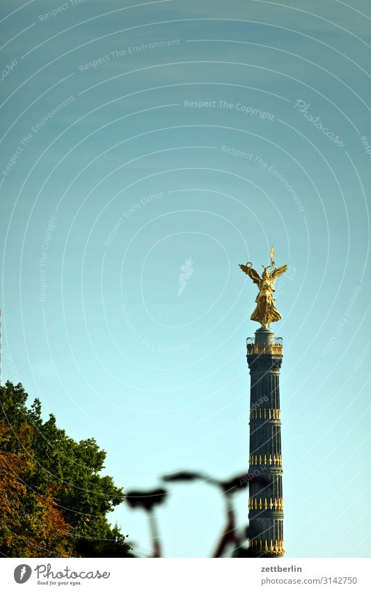 Victory column with blurred bicycle Monument else Goldelse victory statue Victoria big star Berlin zoo Park Forest Tree Downtown Berlin Germany Transport Figure