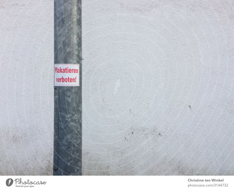 lamppost with sticker 'Placarding prohibited' in front of a dirty white wall Wall (barrier) Wall (building) Lamp post Concrete Metal Signs and labeling Signage