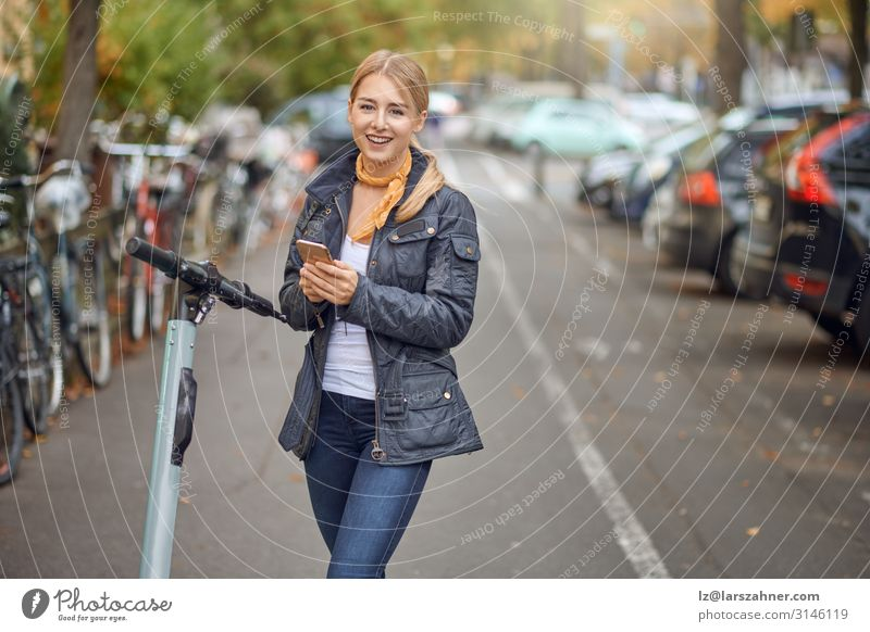 Young woman in the street with e-scooter Lifestyle Happy Beautiful Leisure and hobbies Telephone PDA Technology Woman Adults 1 Human being Autumn Transport