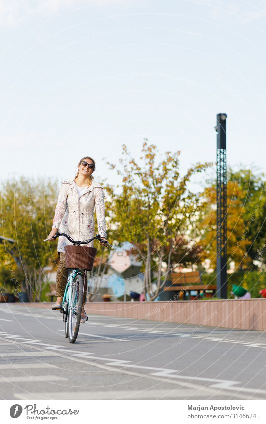 Young woman riding a bicycle in the city Joy Athletic Life Cycling Bicycle Feminine Youth (Young adults) Woman Adults 1 Human being 30 - 45 years Town Transport