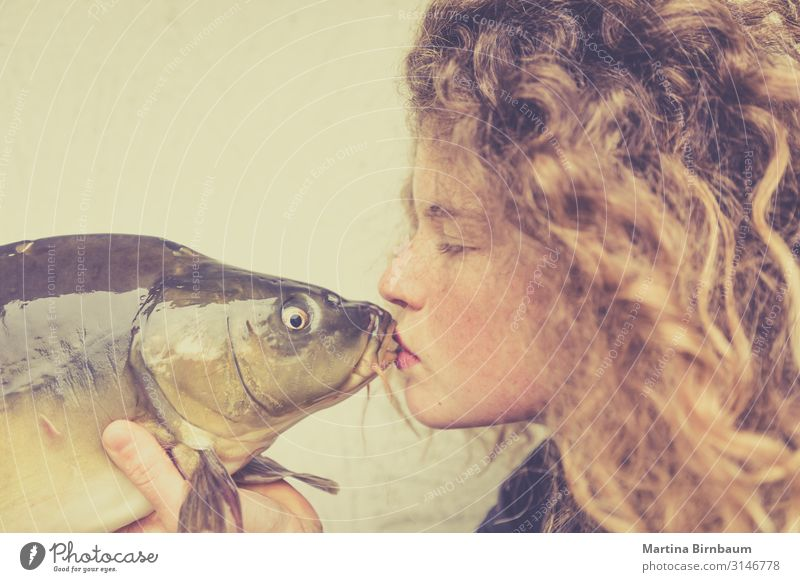 Young woman kissing a carp, fish Seafood Dinner Diet Lifestyle Happy Beautiful Face Human being Feminine Woman Adults Mouth Lips Animal Kissing Love Stand