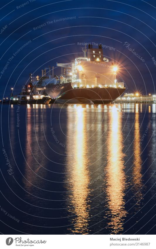 Illuminated ship in a port at night. Ocean Waves Industry Logistics Business Harbour Transport Navigation Oil tanker Watercraft Large LNG tanker LNG carrier