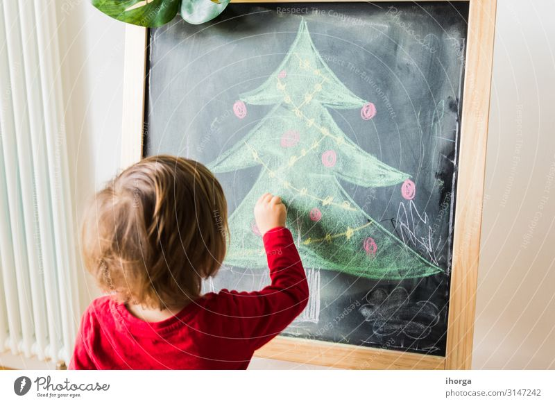 child painting christmas tree on blackboard Lifestyle Joy Beautiful Winter Winter vacation Feasts & Celebrations Christmas & Advent Child Blackboard Human being