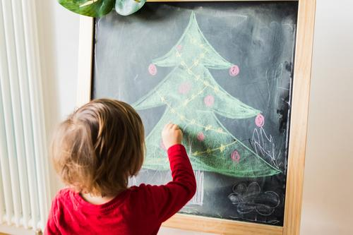 child painting christmas tree on blackboard Lifestyle Joy Beautiful Winter Winter vacation Feasts & Celebrations Christmas & Advent Child Blackboard Human being