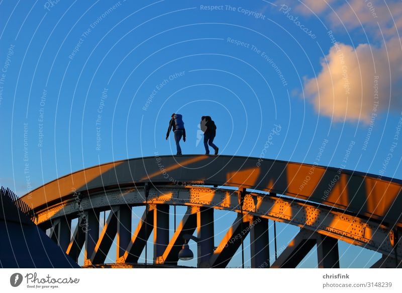 Pedestrians on bridge railings in the evening sun Technology Human being Friendship 2 18 - 30 years Youth (Young adults) Adults Bridge Architecture Street