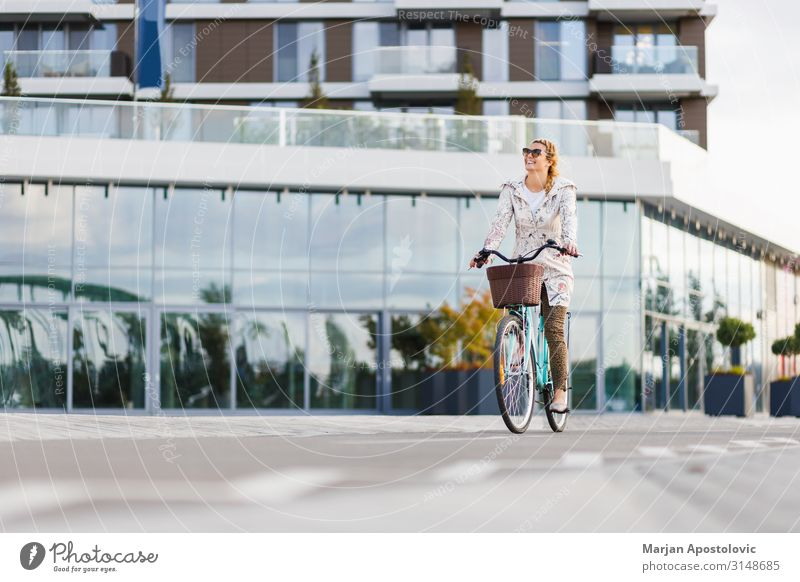 Young happy woman riding a bicycle in the city Lifestyle Joy Leisure and hobbies Cycling Bicycle Feminine Young woman Youth (Young adults) Woman Adults 1