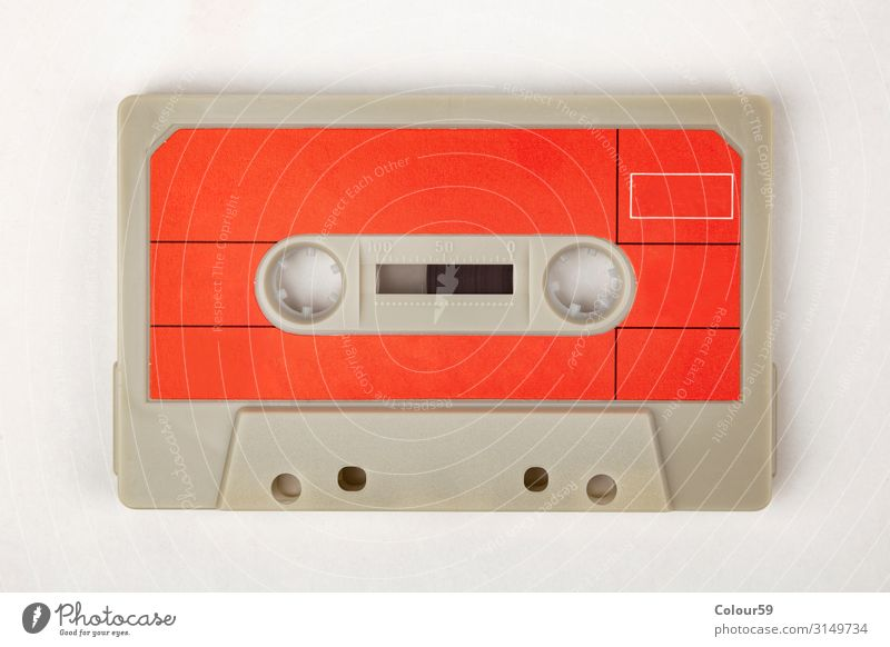 Music cassette with red label Tape cassette Retro audio 80s Disco Background picture Analog Audio tape Iconic Listen to music Colour photo Bird's-eye view
