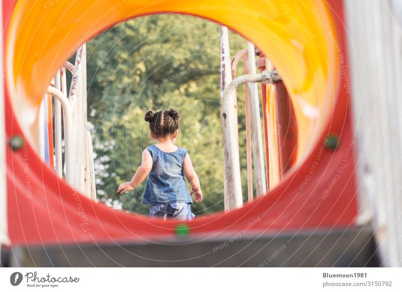 Backside of a little girl having fun in playground area Child Human being Summer Blue Town Colour Green Red Loneliness Joy Girl Healthy Lifestyle Environment