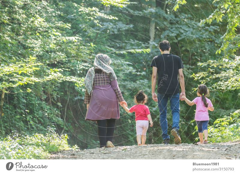 Backside of young family walking together in green nature Child Human being Vacation & Travel Nature Youth (Young adults) Young woman Summer Plant Beautiful